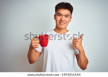 A young man drinks Chinese tea on a background of red Chinese la Photo stock © galitskaya