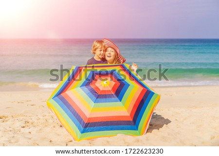 Foto stock: Mother And Son On The Beach In A Hat And Beach Umbrella Vertical Format For Instagram Mobile Story O