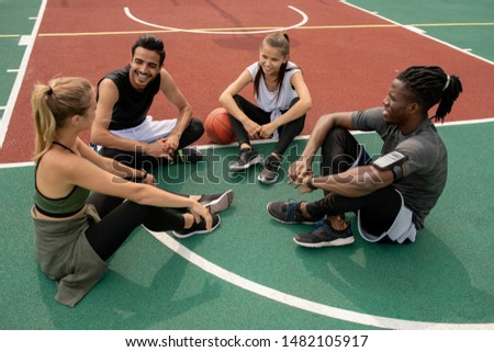 Happy young intercultural friends discussing last game of basketball Stock photo © pressmaster