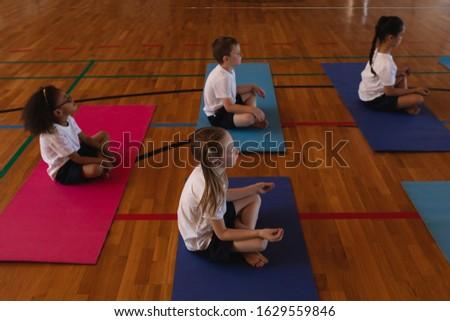 Side view of schoolgirl doing yoga on a yoga mat in school gymnasium Stock photo © wavebreak_media
