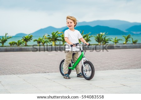 active blond kid boy driving bicycle in the park near the sea toddler child dreaming and having fun stock photo © galitskaya
