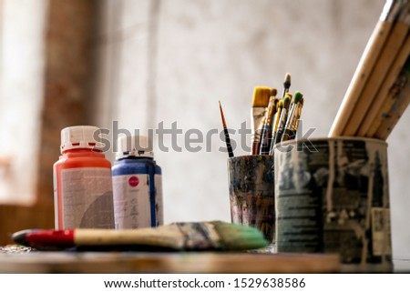 Set of paintbrushes in tin cans and two plastic jars with red and blue gouache Stock photo © pressmaster