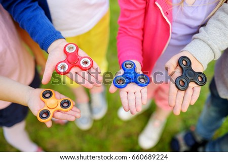 Boy playing with fidget spinner. Child spinning spinner on the playground. Blurred background Stock photo © galitskaya