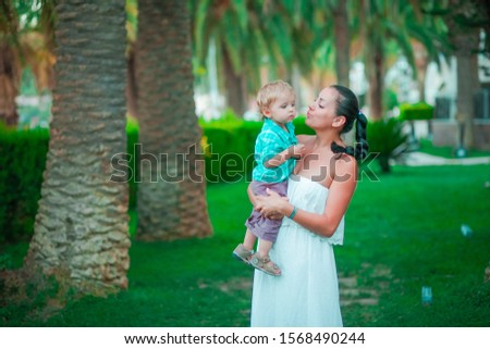 A mother of Oriental appearance holds a small child with blond hair against a background of green gr Stock photo © ElenaBatkova