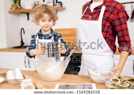 Cute little boy sifting flour while standing by table next to his mom Stock photo © pressmaster