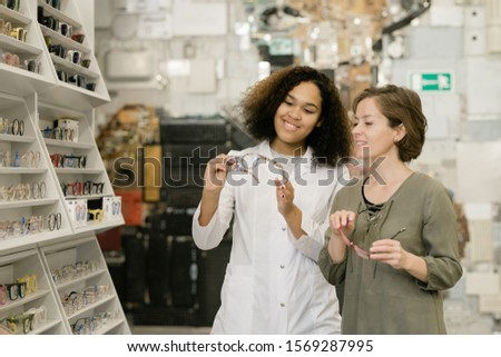 Young successful consultant of optics shop showing one of new models to client Stock photo © pressmaster