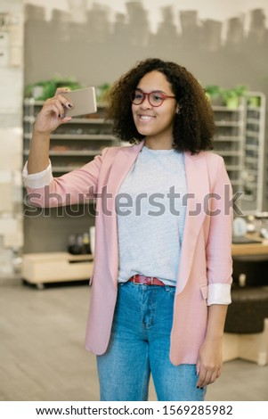 Happy mixed-race girl in smart casual making selfie while trying on new eyewear Stock photo © pressmaster