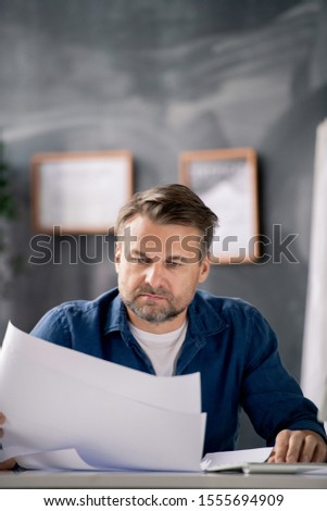 Bearded middle aged architect in casualwear looking at blueprint with sketch Stock photo © pressmaster