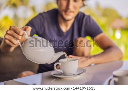 Man with a cup of tea on the cafe veranda near the rice terraces on Bali, Indonesia Stock photo © galitskaya