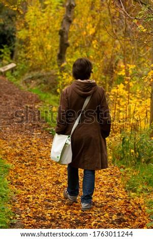 A woman in a yellow coat and short hair walks around the city Stock photo © ElenaBatkova