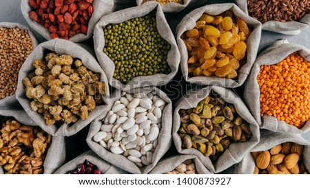 Horizontal shot of various protein seeds, beans and grains poured out from glass bottles on grey sur Stock photo © vkstudio
