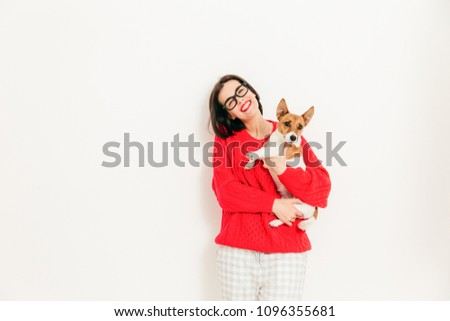 Photo of delighted Caucasian female carries jack russell terrier dog, wears spectacles and red sweat Stock photo © vkstudio