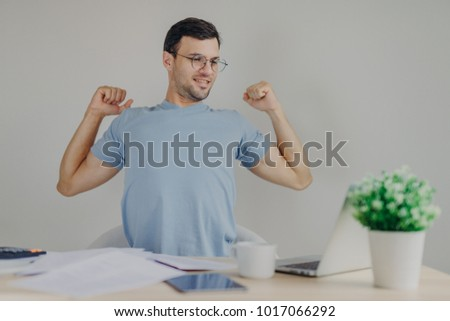 Overworked male freelancer stretches at work place, just finishes with work, looks happily into scre Stock photo © vkstudio