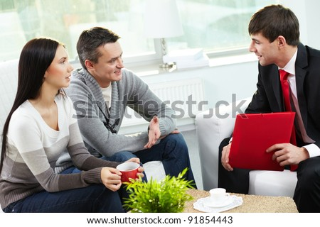 portrait of a happy young couple talking with agent while signin stock photo © hasloo