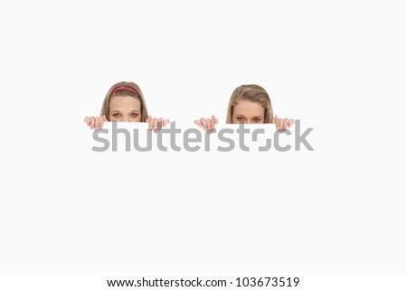 Close-up of young women behind a blank sign against white background stock photo © wavebreak_media