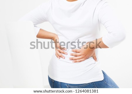 Woman sitting on a table while touching her back in a medical room Stock photo © wavebreak_media