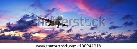 Stock photo: Jet is maneuvering for landing in a sunset sky. Panoramic compos