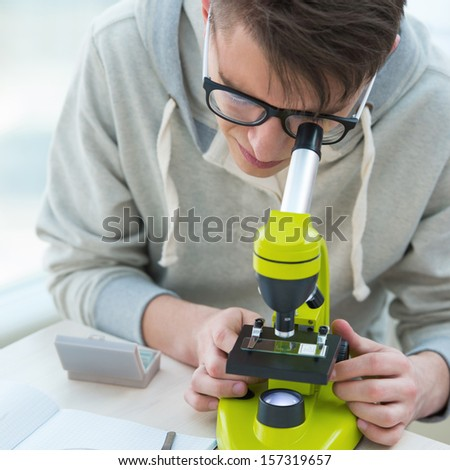 High School students. Handsome guy working at biology classroom: Stock photo © HASLOO