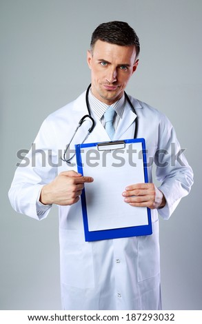 dissatisfied male doctor with clipboard and stethoscope standing over a white background Stock photo © deandrobot