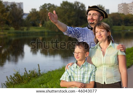 Family in fall evening park near pond: man in pirate suit, woman and little boy. man is point away Stock photo © Paha_L