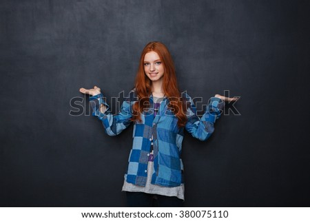 happy woman holding copyspace on two palms over blackboard background stock photo © deandrobot