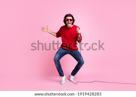 charismatic positive young man singing in microphone and playing guitar stock photo © deandrobot