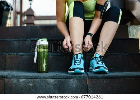 Green detox smoothie cup and woman lacing running shoes before w Stock photo © dashapetrenko