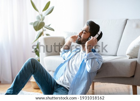Adult male enjoying listening to favorite music podcast on headp Stock photo © stevanovicigor