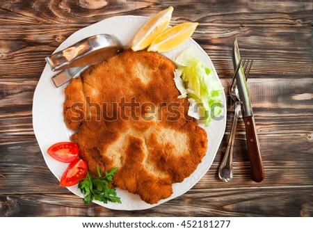fried pork chop coat in breadcrumbs with lemon slise and vegetab stock photo © yatsenko