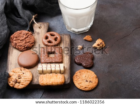 oat and chocolate cookies selection with glass of milk on wooden board on stone kitchen table backgr stock photo © denismart