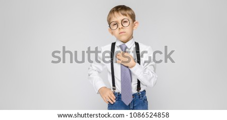A charming boy in a white shirt, suspenders, a tie and light jeans stands on a gray background. A bo Stock photo © Traimak