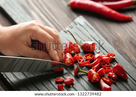 organic ripe peppers cut the hands of a woman on a wooden board on the kitchen table tomatoes and stock photo © artjazz