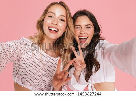 Women friends isolated over pink wall background showing peace gesture. Stock photo © deandrobot