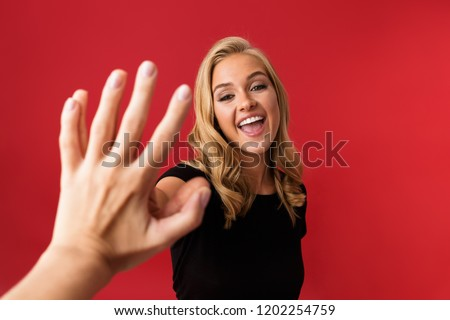 Excited woman looking camera give a high five to someone's hand isolated over red background. Stock photo © deandrobot