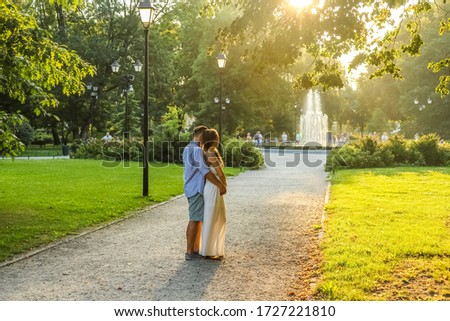 Beautiful smiling love couple sitting near fountain on a sunny d Stock photo © boggy