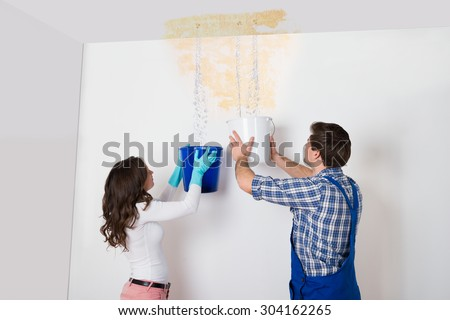 Woman And Repairman With Collecting Water From Damaged Ceiling Stock photo © AndreyPopov