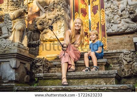 Mom and son tourists in Ubud palace, Bali - Inside the Ubud palace, Bali, Indonesia. Traveling with  Stock photo © galitskaya