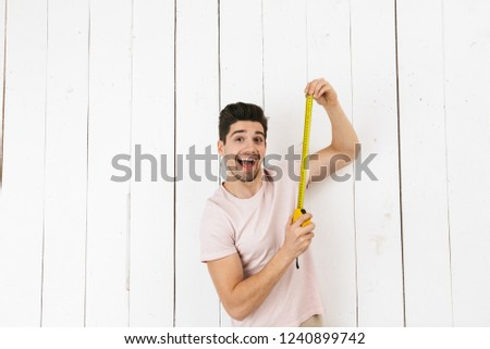 Portrait of masculine man 20s holding yellow ruler for measureme Stock photo © deandrobot