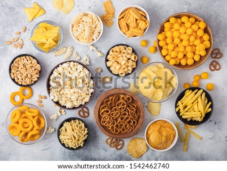 All classic potato snacks with peanuts, popcorn and onion rings and salted pretzels in bowl plates o Stock photo © DenisMArt