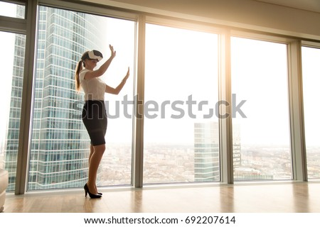 Young smiling female employee with vr headset touching virtual stuff Stock photo © pressmaster
