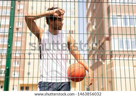 Adolescent basketball player in activewear leaning against fence of the court Stock photo © pressmaster