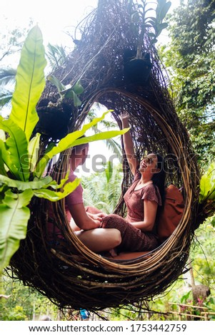 a tourist couple sitting on a large bird nest on a tree at bali stock photo © boggy