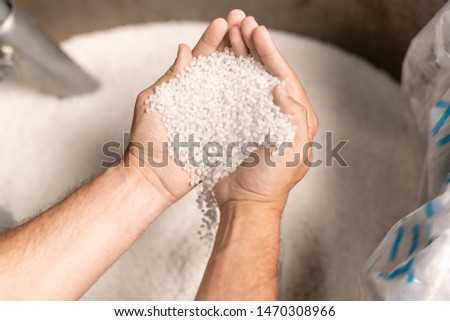 View of modern factory worker hands holding pile of white polymer pellets Stock photo © pressmaster