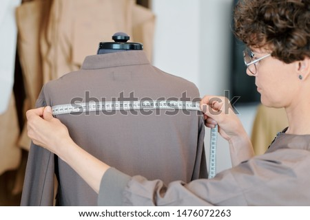 Young female tailor measuring back width of grey jacket on mannequin Stock photo © pressmaster
