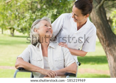 front view of disabled senior woman smiling with her happy friends behind in living room at home stock photo © wavebreak_media