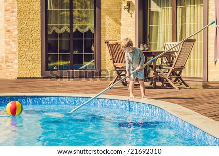 The Toddler boy cleans the pool and pulls the ball out of the pool. Pool Cleaner Concept Stock photo © galitskaya