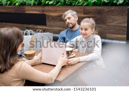 Pretty girl and her mother with paperbag looking at one another by table in cafe Stock photo © pressmaster
