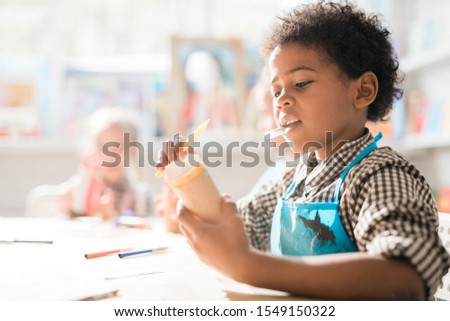 Contemporary schoolboy with crayon rolling piece of paper while making toy Stock photo © pressmaster