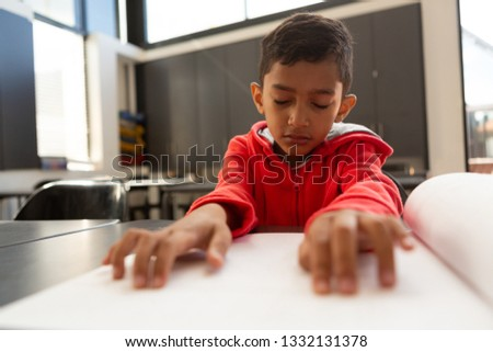 Front view of blind mixed-race schoolboy reading a braille book at desk in a classroom at elementary Stock photo © wavebreak_media