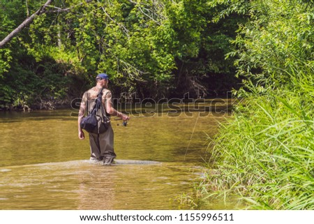 Man fishing on a mountain river with a ultralight spinning using fishing wobblers. He got his hook h Stock photo © galitskaya